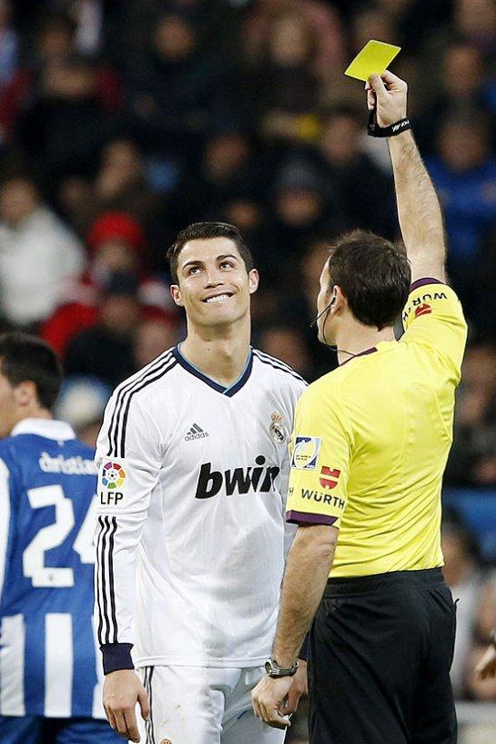 O árbitro Miguel Mateu Lahoz dá cartão amarelo a Cristiano Ronald em jogo do Real contra o Espanyo