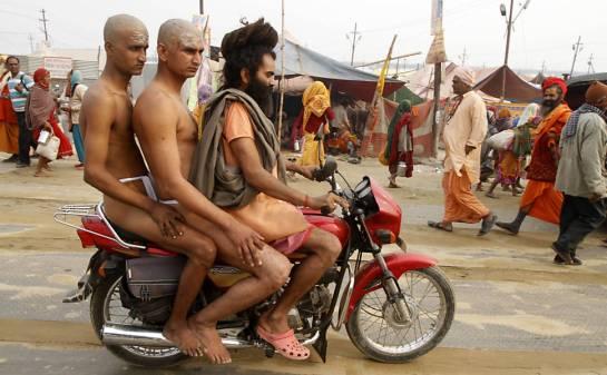 Dois homens sagrados hindus da seita Juna Akhara pegam carona de moto para os rituais na cidade de Allahabad (Índia)